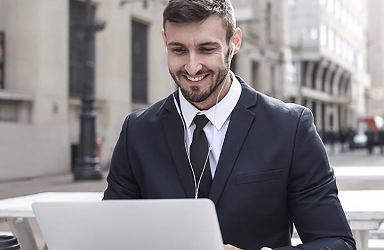 junger mann im anzug laechelnd am laptop mobil