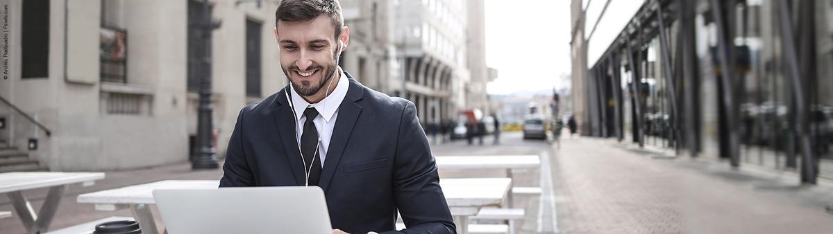 junger mann im anzug laechelnd am laptop tablet