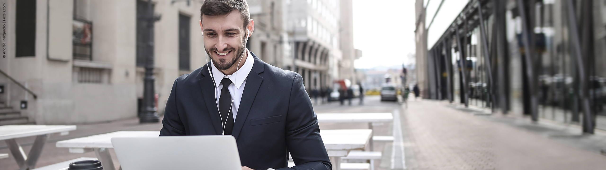 junger mann im anzug laechelnd am laptop