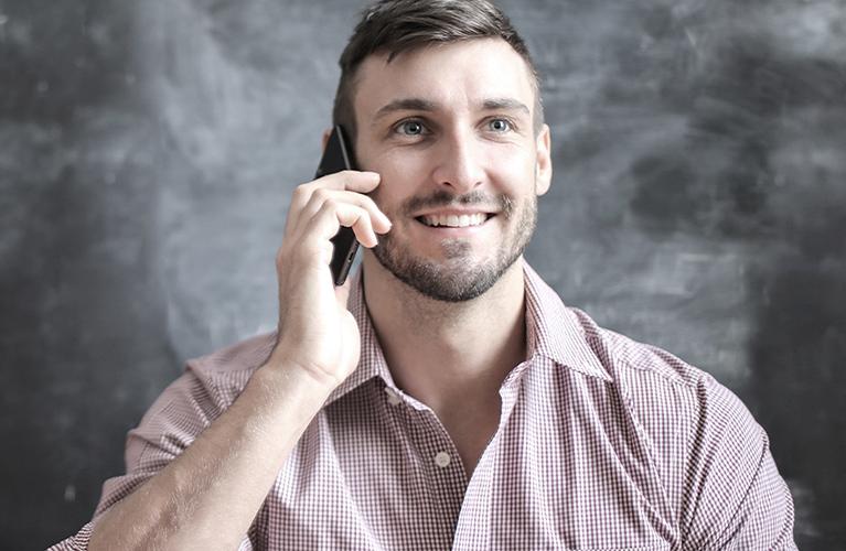 junger mann laechelnd am telefon mobil