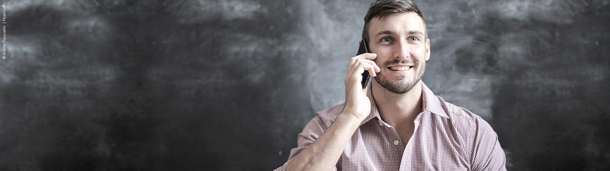 junger mann laechelnd am telefon tablet