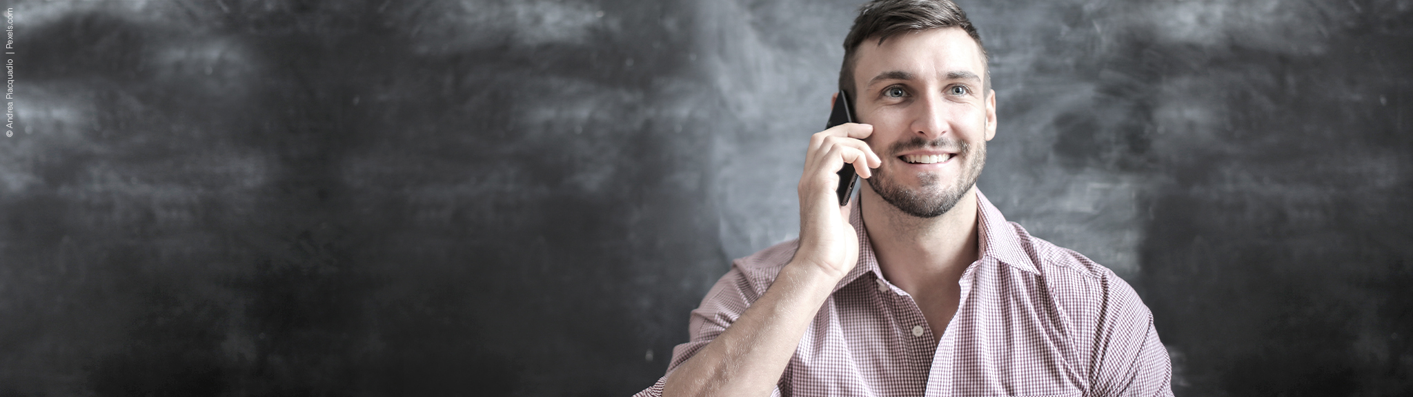 junger mann laechelnd am telefon